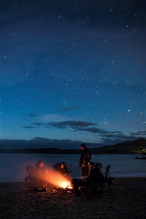A team enjoying a campfire under the stars on a Pembrokeshire beach