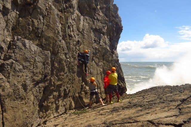 Girl on a rock-climbing on the Gower coast near Swansea