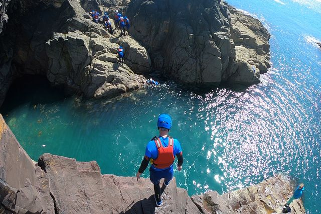 Guy readies himself for a coasteering jump in Pembrokeshire