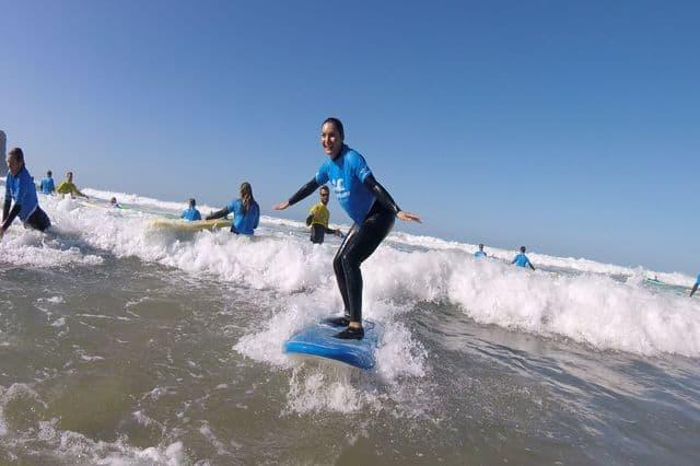 Girl surfing a wave in Arrifana, Algarve