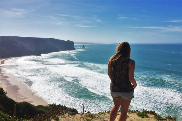 Girl overlooking Praia da Arrifana on a hiking activity in Algarve
