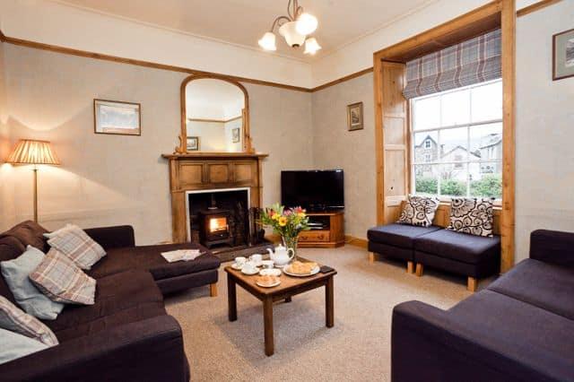 Living room with log burner in private group cottage Beddgelert, North Wales