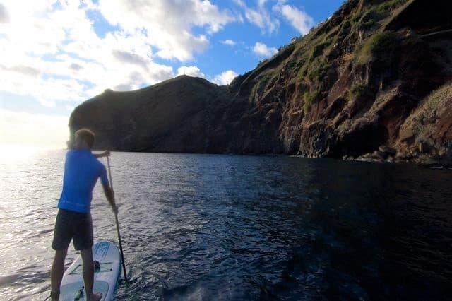A guy enjoying a paddleboarding activity on the coast of Madeira
