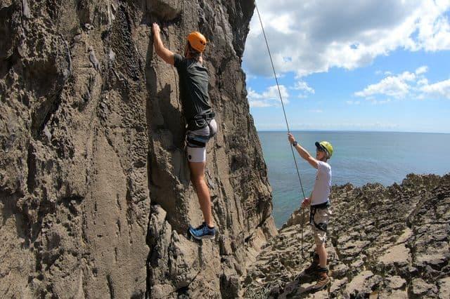 A guy enjoying rock-climbing on the coast of Swansea In Wales