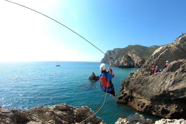 A girl on a zipline whilst coasteering on the coast of Lisbon